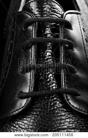 Lace-up of black oxford polished shoes on black background.Shoes shine. Close up.