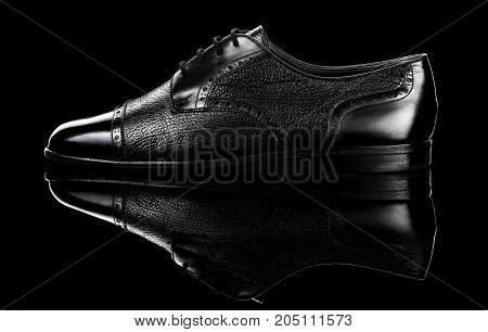 Black oxford polished shoes on black miror background.Shoes shine.