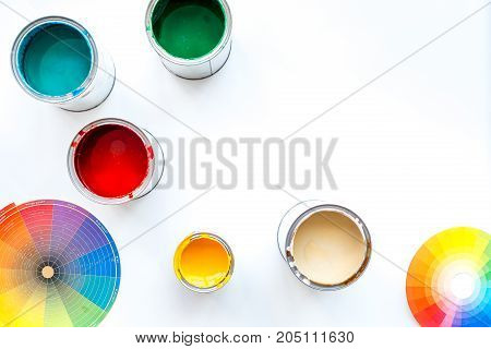 Choosing color for painting. Palette and paints in tin banks on white background top view.