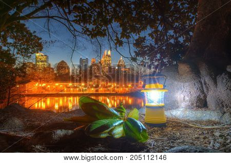 Luminous hand lantern standing on the ground of Piedmont Park on the background of Midtown Atlanta at dusk