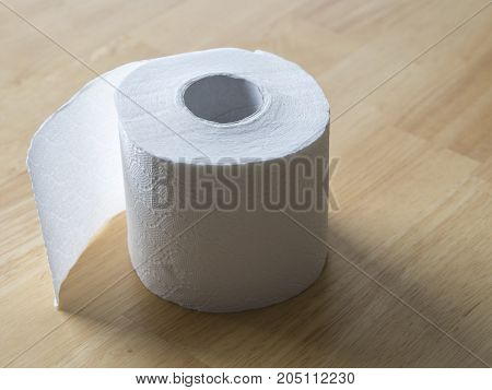 close up white roll of toilet paper on wooden background