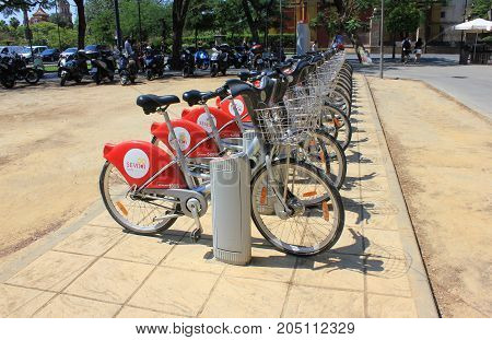 SEVILLE, SPAIN - JUNE 9, 2017: Bike rental station at downtown street. Row of new bikes ready for service on busy tourist season. Simple and cheap way for transfers and travelling across the city.n through the busy downtown