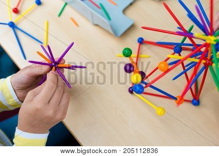 Two Little Girls Playing With Lots Of Colorful Plastic Sticks Kit Indoors. Kids Having Fun With Buil