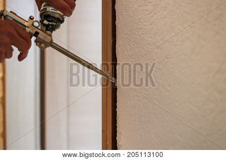 Young Handyman Installing Door With An Mounting Foam In A Room.
