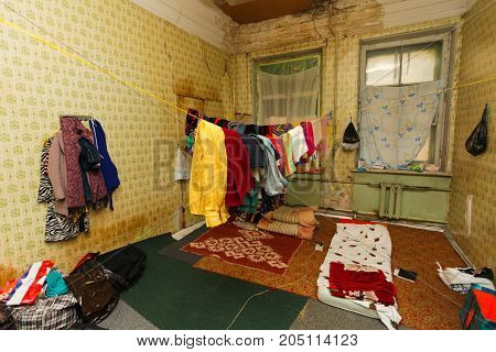 Refugees' clothes is dried on the rope in the temporary dirty old apartment and sleeping place on the floor for refugees