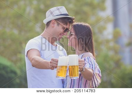 Young hipster couple in love cheering with beer stains at the city street