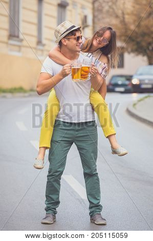 Young hipster couple in love cheering with beer mugs at the city street