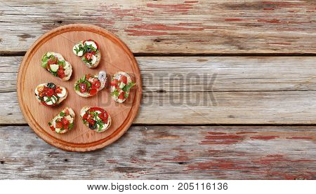 Delicious Italian Bruschetta With Roasted Tomatoes, Mozzarella Cheese And Herbs On A Cutting Board