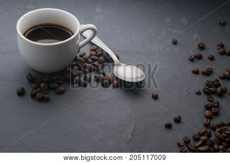 Coffee cup with a spoon and some coffee beans