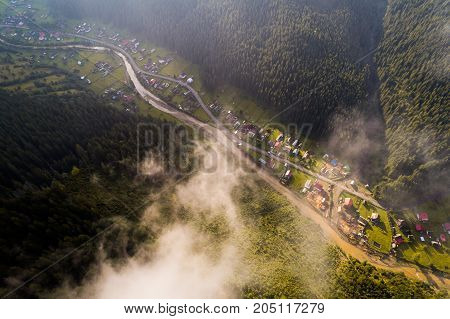Beautiful nature landscape aerial view of the village in the Carpathian mountains with clouds in the foreground and sun rays. Top view. From above