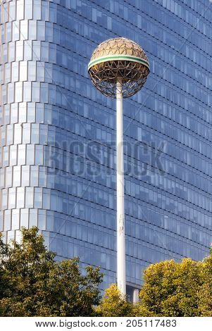 An abstract shape on a post in front of a glass building in Nanjing China Jiangsu province.