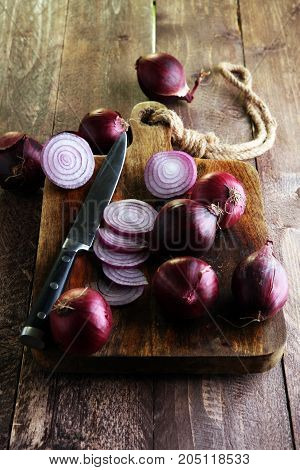 Red Onions Circles And Red Onions On Board Against Wooden Backgr
