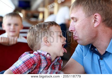 Father with son show their tongues in cafe