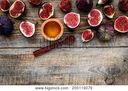 Fresh blue figs and honey on wooden background top view.
