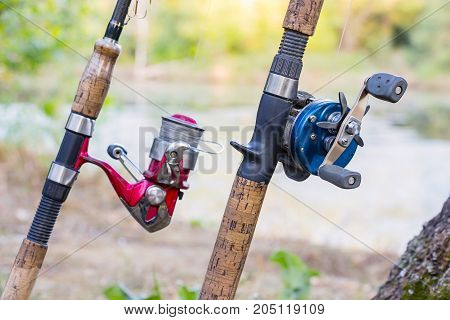 Two fishing rods with reels. One reel spinning and second baitcasting reel. Blurred background