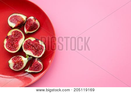 Fresh blue figs on plate on pink background top view.