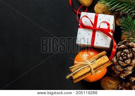 Christmas New Year Composition Greeting Card. Tangerine Cinnamon Sticks Pine Cones Fir Tree branches Gift Box with Curled Red Ribbon Nuts on Dark Background. Template Copy Space.