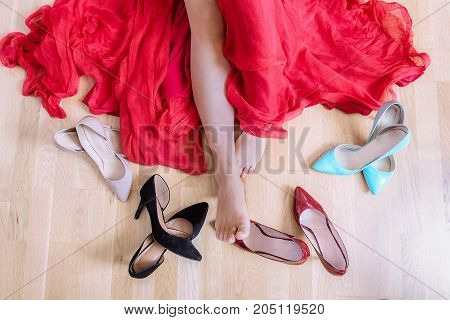 Above image with the bare feet of a Caucasian woman dressed in a red dress laying on the floor and surrounded by high heels shoes.
