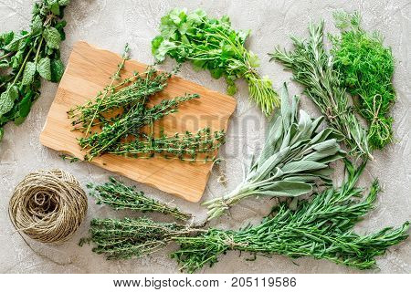 fresh herbs and greenery for spices and cooking on stone kitchen desk background top view