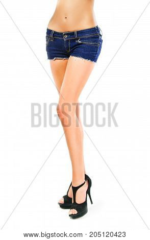 Female legs in black shoes and denim shorts.