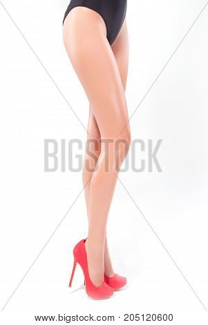 Slender female feet in red high-heeled shoes