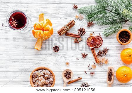 Hot mulled wine or grog cooking for new year celebration with oranges and spices ingredients on light table background flat lay