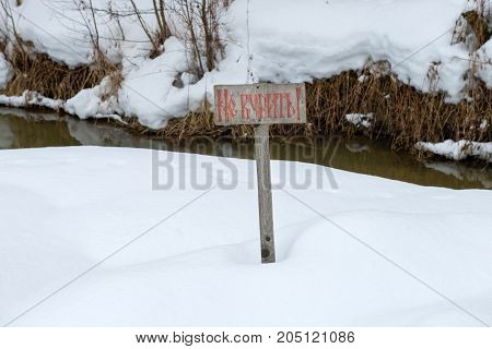 The tablet is forbidden to smoke in the deep snow on the riverbank in the park