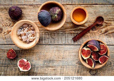 Make jam. Fresh blue figs in bowl and honey on wooden background top view.