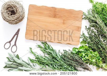 making spices with fresh herbs and greenery for cooking on white kitchen table background top view mockup