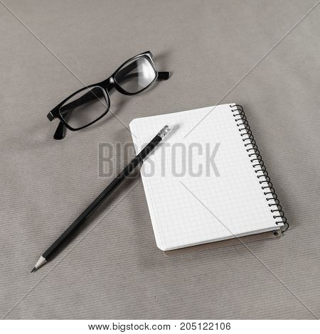 Blank notebook glasses and pencil on craft paper background.