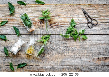 Medicinal herb in bottles on wooden background top view.