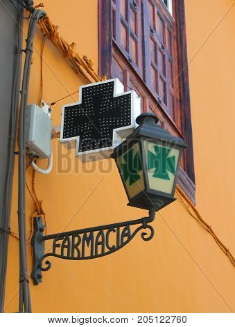 old spanish pharmacy sign in wrought iron on a yellow wall with green cross farmacia = pharmacy