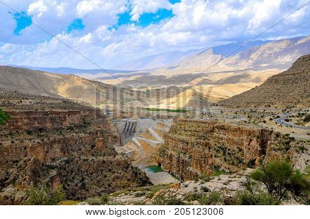 road in the hilly terrain of Iran runs along a big kanyen the dam nearby settles down