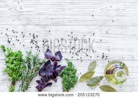 natural oil and fresh greenery for restaurant cooking with spices on wooden kitchen table background top view space for text