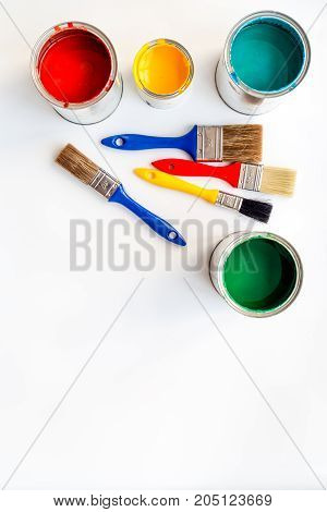 Paints in tin banks and brushes on white background top view.