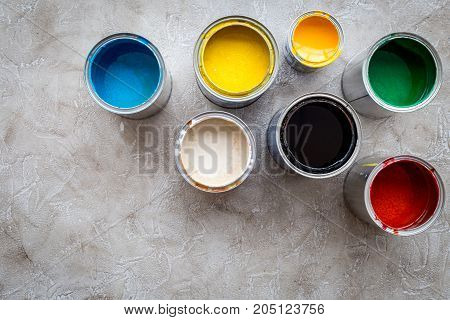 Paints in tin banks on grey stone background top view