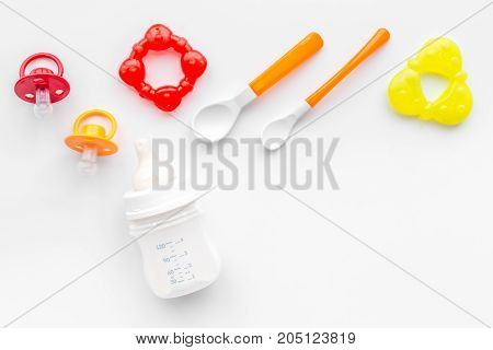 preparation of mixture baby feeding with infant formula powdered milk in bottle with spoons on white desk background top view mockup