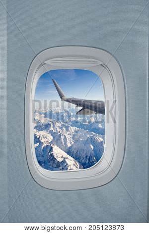 Airplane window with view over the Alps