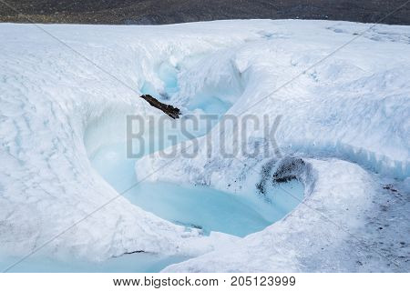 Milky blue meltwater running from Longyearbyen glacier in Svalbard. Glacier covered by light snowfall.