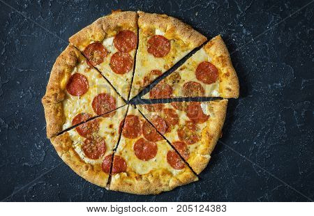 Pepperoni pizza on rustic vintage style. Top view on dark stone table