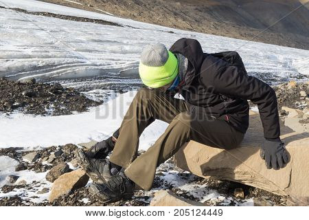 Young man attaching ice spikes to his shoes to walk on glacier. Longear glacier in Svalbard in background.