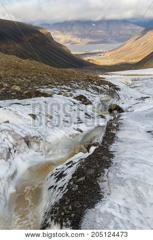 Svalbard - Longyear valley and the edge of Longyear glacier with running meltwater. Longyear valley showing rich geological diversity. Longyearbyen Adventfjorden and mountain Hiorthfjellet covered in clouds in background.