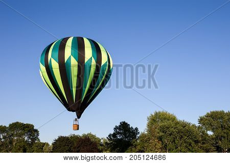 Colorful hot air balloon floating at tree top level. Copy space in right part of frame.