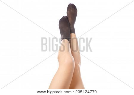 Female legs with black nylon socks on a white background isolation