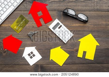 selling property online set with paper house on office desk wooden background top view