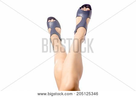 Female legs of blue sandals with heels shoes on white background isolation