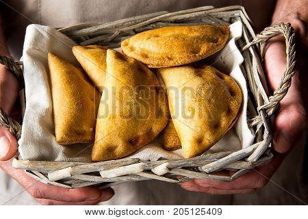Man chef holding in hands a wicker basket with freshly baked vegetarian empanadas turnover pies with vegetables cheese in tomato sauce. Authentic kinfolk atmosphere. Cozy home.