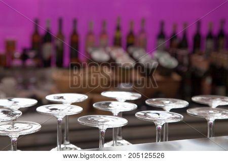 Alcohol bar concept photo, glasses at bottle violet background