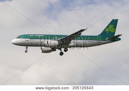 LONDON UK - AUGUST 6 2013; An Aer Lingus Airbus A320-214 (EI-DEJ) lands on a cludy day at Heathrow airport in London
