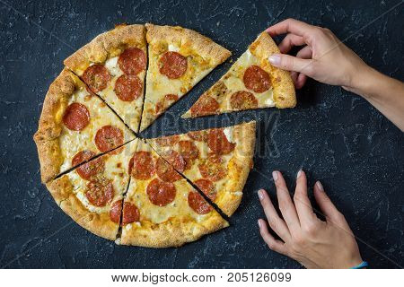 Pepperoni pizza on rustic vintage style. Top view on dark stone table. Female hands.